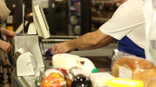 vídeos y material grabado en eventos de stock de escáner de código de barras de la tienda de comestibles en el supermercado compras, - mostrador de tienda para pagar