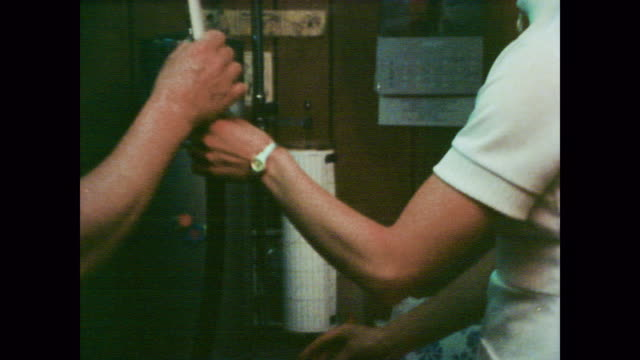 1978 bare chested asbestos worker breathes into a tube as technician works medical testing machine - アスベスト点の映像素材/bロール