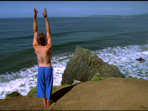 bare chested man in blue cropped pants stretches arms on cliff as part of yoga exercise, california - human limb stock videos & royalty-free footage