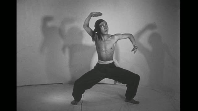 1948 bare chested man (chao-li chi) performs shadow boxing moves in slow motion in an empty room - 少林寺点の映像素材/bロール