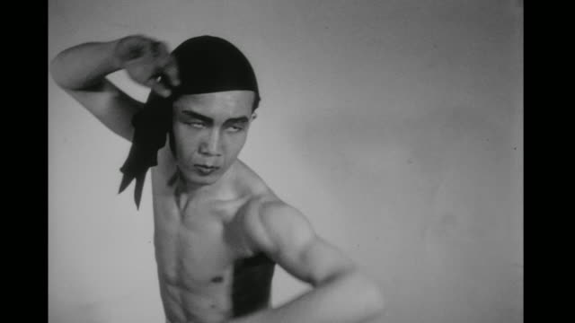 1948 bare chested man (chao-li chi) performs shadow boxing moves, including roundhouse leg kicks, in slow motion in an empty room - 少林寺点の映像素材/bロール