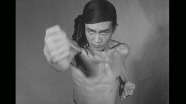 1948 bare chested man (chao-li chi) performs shadow boxing moves, including sweeping round house kicks and double-fisted attack sequences all in slow motion - 少林寺点の映像素材/bロール