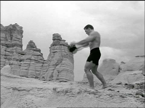 vídeos de stock, filmes e b-roll de b/w bare chested muscular man on rock formation throwing discus - machos
