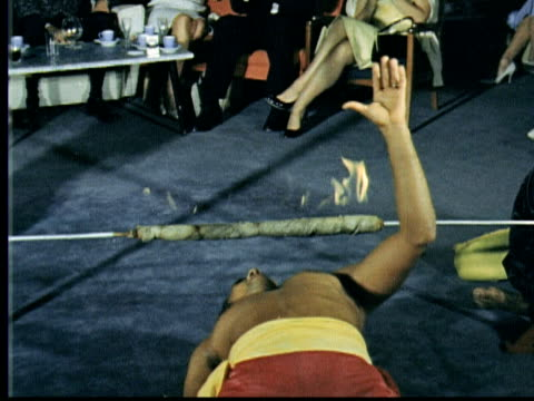 bare chested young man does limbo under flaming limbo stick jonathan winters lights his cigarette / hamilton bermuda - one man only stock videos & royalty-free footage