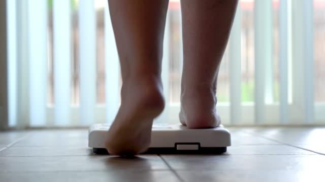彼女の体重をチェックするために浴室のスケールに踏んでいる女性の裸の足と脚 - 体重計点の映像素材/bロール