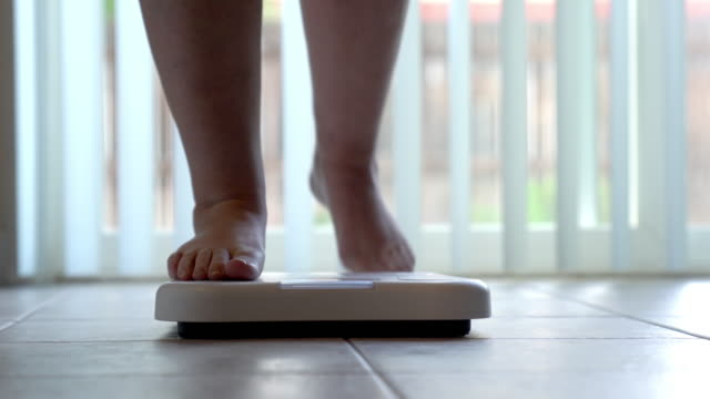 vídeos de stock e filmes b-roll de bare feet and legs of a woman stepping onto a bathroom scale to check her weight - passos