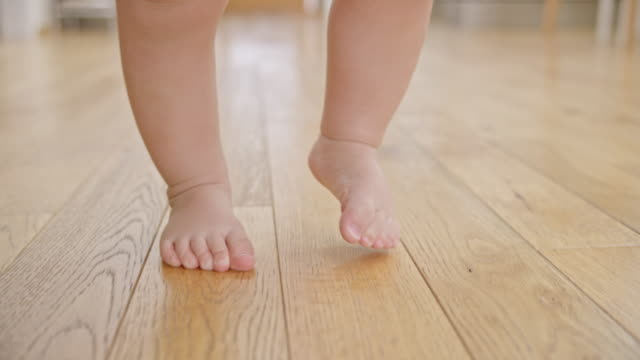 slo mo bare feet of a baby walking on wooden floor - primi passi video stock e b–roll