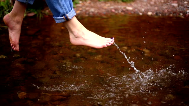 Bare feet of a woman. river water.