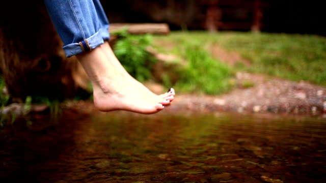 Bare feet of a woman. river water