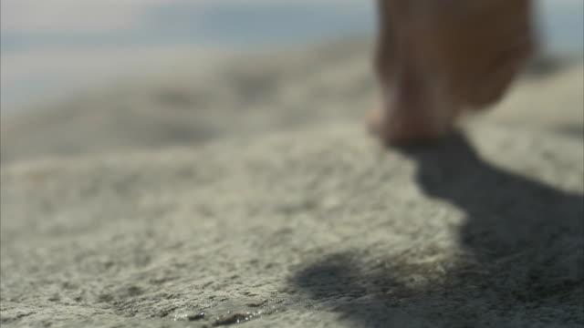 Bare feet walking on cliffs close-up Huvudskar Stockholm archipelago Sweden.