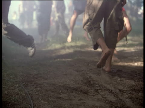 stockvideo's en b-roll-footage met bare feet walking on dusty path towards campsite as others run in opposite direction england - tent
