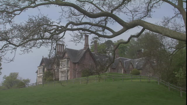bare tree branches frame the culver house up on a hillside. - stately home stock videos & royalty-free footage