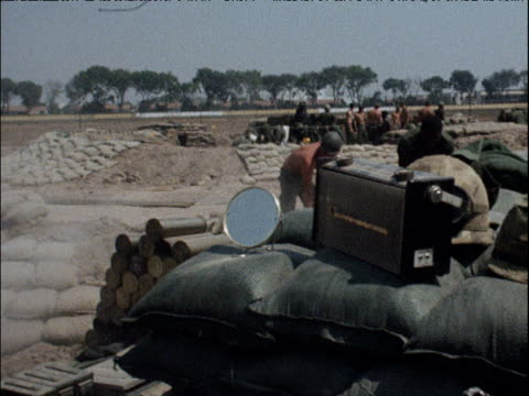 vídeos de stock, filmes e b-roll de barechested american troops dig around army camp old style radio and shaving mirror in foreground pan left to more troops unloading sandbags from... - 1964
