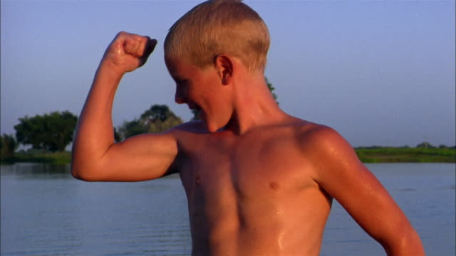 a bare-chested pre-teen boy flexes his arms to show off his pecs. - visa musklerna bildbanksvideor och videomaterial från bakom kulisserna