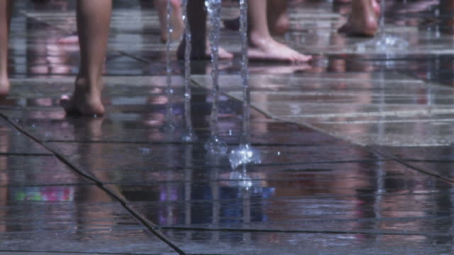 barefeet running and playing in a splash pad fountain. - barefoot点の映像素材/bロール