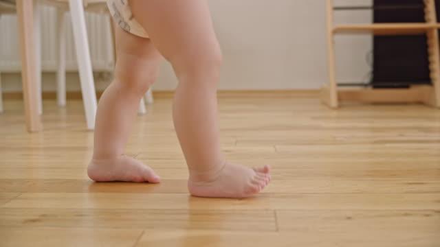 木製の床の上を歩いて slo mo 裸足の赤ちゃん - 赤ちゃんのみ点の映像素材/bロール
