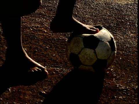 CU,  barefoot boy holding foot on soccer ball,  close up of feet,  Hout Bay, Cape Town, South Africa