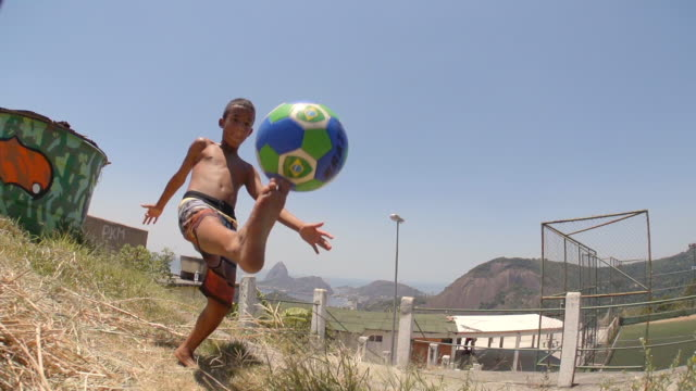 barefoot boy juggles brazilian soccer ball on hillside and kicks ball at camera in slow motion - favela stock videos and b-roll footage