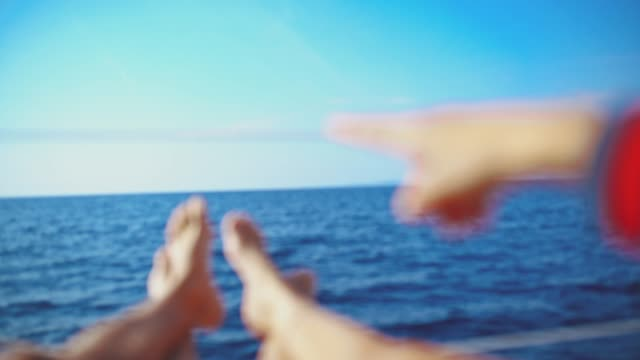 4k barefoot couple relaxing, pointing on sunny sailboat, real time - barca da diporto video stock e b–roll