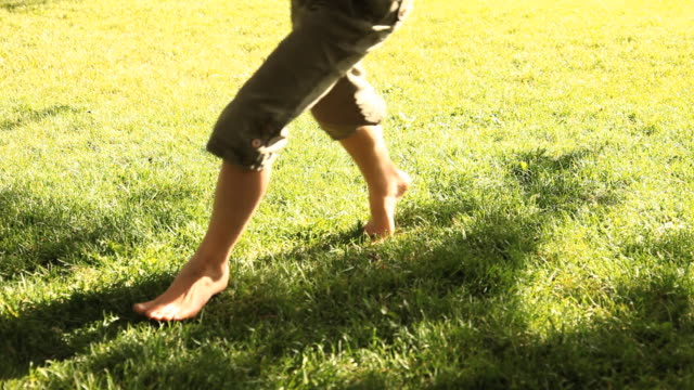 CU Barefoot girl (6-7) and boy (4-5) running on grass, low section, Flagstaff, Arizona, USA