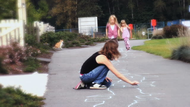 vidéos et rushes de ws  a barefoot girl hopscotching  running on sidewalk / langley, british columbia, canada. - trottoir