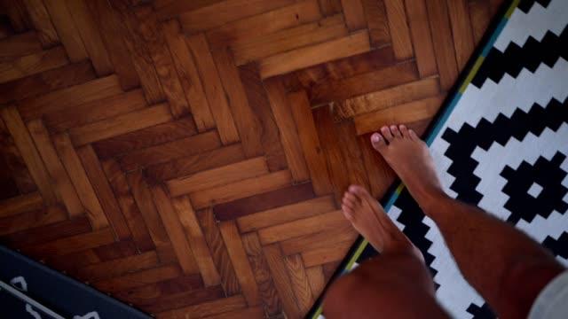 stockvideo's en b-roll-footage met barefoot benen lopen op de houten vloer - hoog standpunt