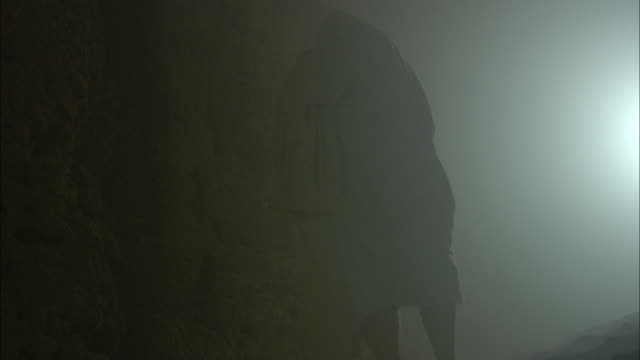 a barefoot man in a galabiya passes through a foggy cave in cairo, egypt. - barefoot stock videos & royalty-free footage