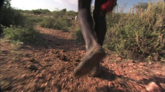 A barefoot man walks along dry ground.