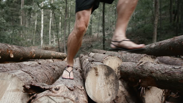 SLO MO DS Barefoot runner running over a stock of logs in the forest