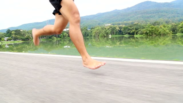 barefoot running on road in the park with mountain background - barefoot stock videos & royalty-free footage