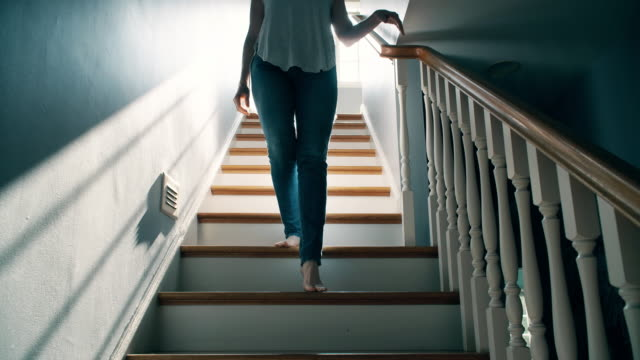 barefoot woman going down a staircase - moving down video stock e b–roll