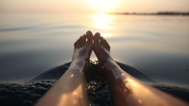 夏休みに海でくつろぐ裸足の女性。ボートに座っている間に水の中の女性の足 - 日光浴点の映像素材/bロール