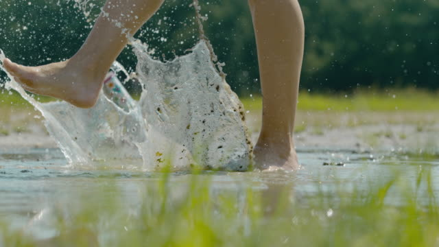 slo mo barefoot woman splashing in the muddy puddle. happy woman. - focus on foreground stock videos & royalty-free footage