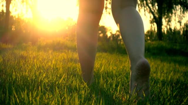 vídeos de stock, filmes e b-roll de mulher com os pés descalços andando na grama - grama