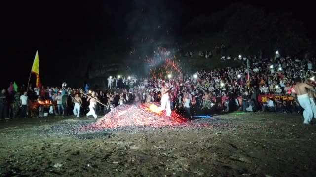 a barefooted man walks through burning charcoal as he performs 'lianhuo' or 'fire walking' to celebrate the double ninth festival on october 7 2019... - traditional festival stock videos & royalty-free footage