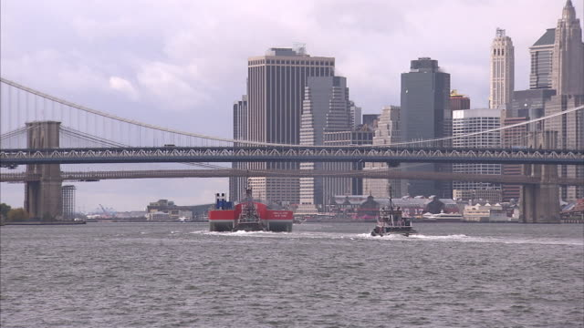 A barge and a tugboat cruise past the Williamsburg Bridge near Manhattan.