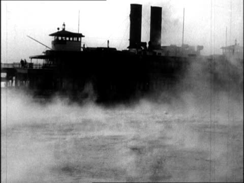 barge and ferryboat moving slowly in ny harbor in windy snowstorm / men chipping ice from rail of ship after snowstorm / man chipping ice from mast... - 1934 個影片檔及 b 捲影像