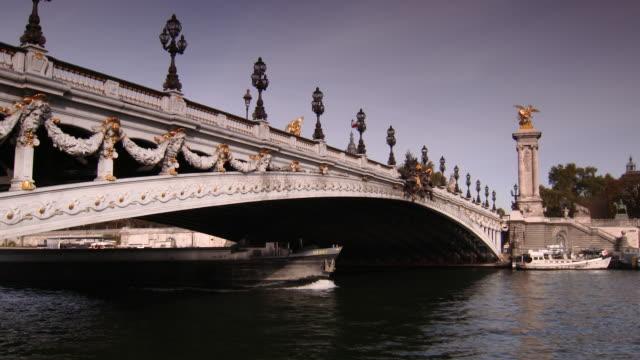 vídeos de stock, filmes e b-roll de barge boat travelling under pont alexander iii on river seine, paris, france - cupido