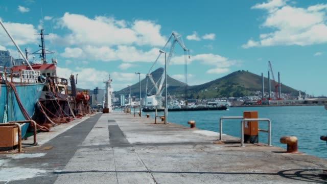 vídeos y material grabado en eventos de stock de a barge carrying a crane sails across the cape town harbour. available in hd. - pasear en coche sin destino