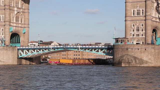 barge carrying ship which transports cargo container is passing under tower bridge - river thames stock videos & royalty-free footage