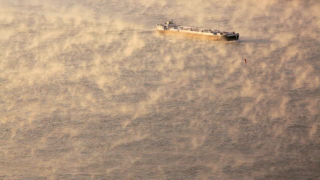 vídeos de stock, filmes e b-roll de a barge cruises across a mist covered rhine river. - passear sem destino