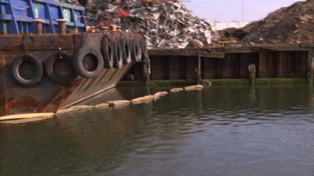 a barge floats near a dock covered in garbage. - barge stock videos & royalty-free footage