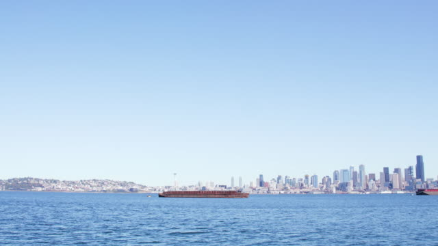 barge floats outside seattle, wide cityscape - nordpazifik stock-videos und b-roll-filmmaterial