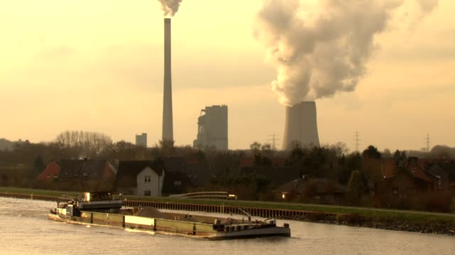Binnenschiff vor Industrieanlage. Ship crossing industiral plant