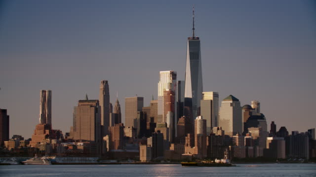 Barge moves slowly along the Hudson River in front of a Lower Manhattan backdrop on a clear evening.