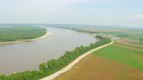 ws aerial pov barge moving in mississippi river with large field area and forest area / illinois, united states - illinois stock videos & royalty-free footage