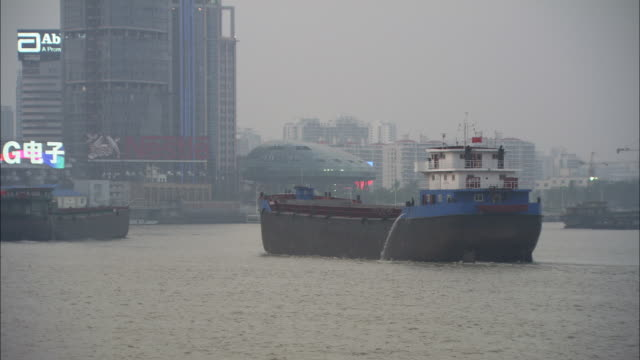 WS PAN Barge on Huangpu River and illuminated neon signs on buildings, Shanghai, China