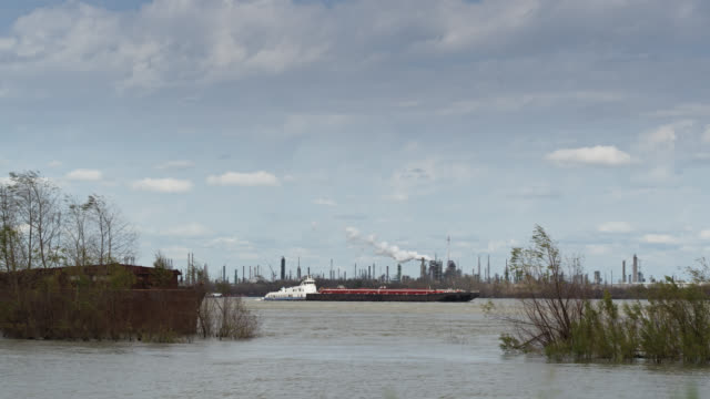 barge on the mississippi passing oil refinery in baton rouge - louisiana stock videos & royalty-free footage