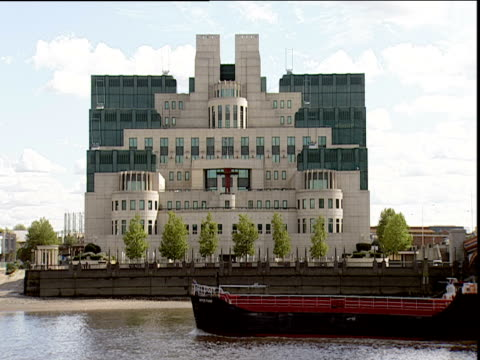 barge passes in front of post-modernist mi6 building on banks of river thames vauxhall - mi6 stock-videos und b-roll-filmmaterial