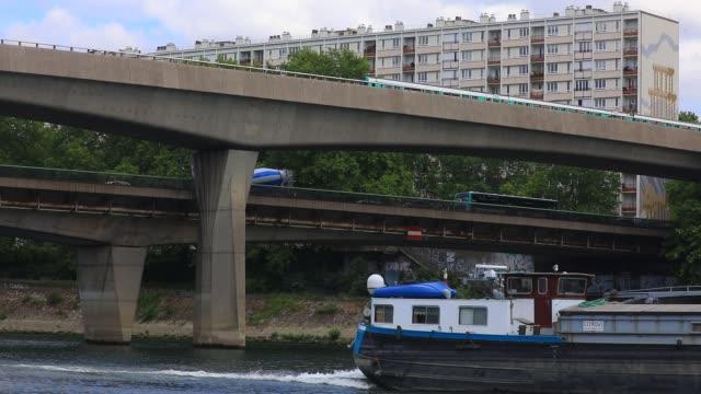barge passes under the metro bridge next to seine river banks on june 18, 2020 in asnieres sur seine, france - vorort wohnsiedlung stock-videos und b-roll-filmmaterial